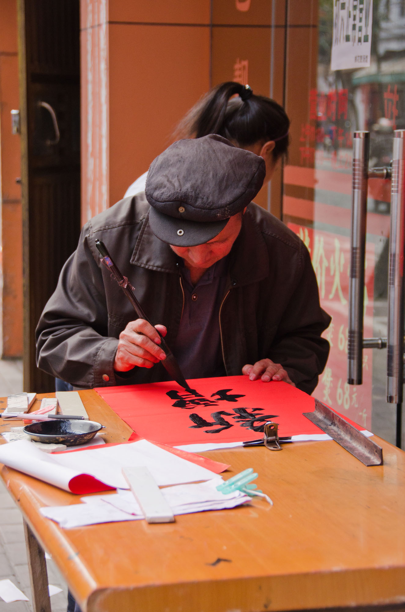Un peintre de Tue Lien dans un vieux quartier de Zhanjiang, avant le Nouvel An Chinois